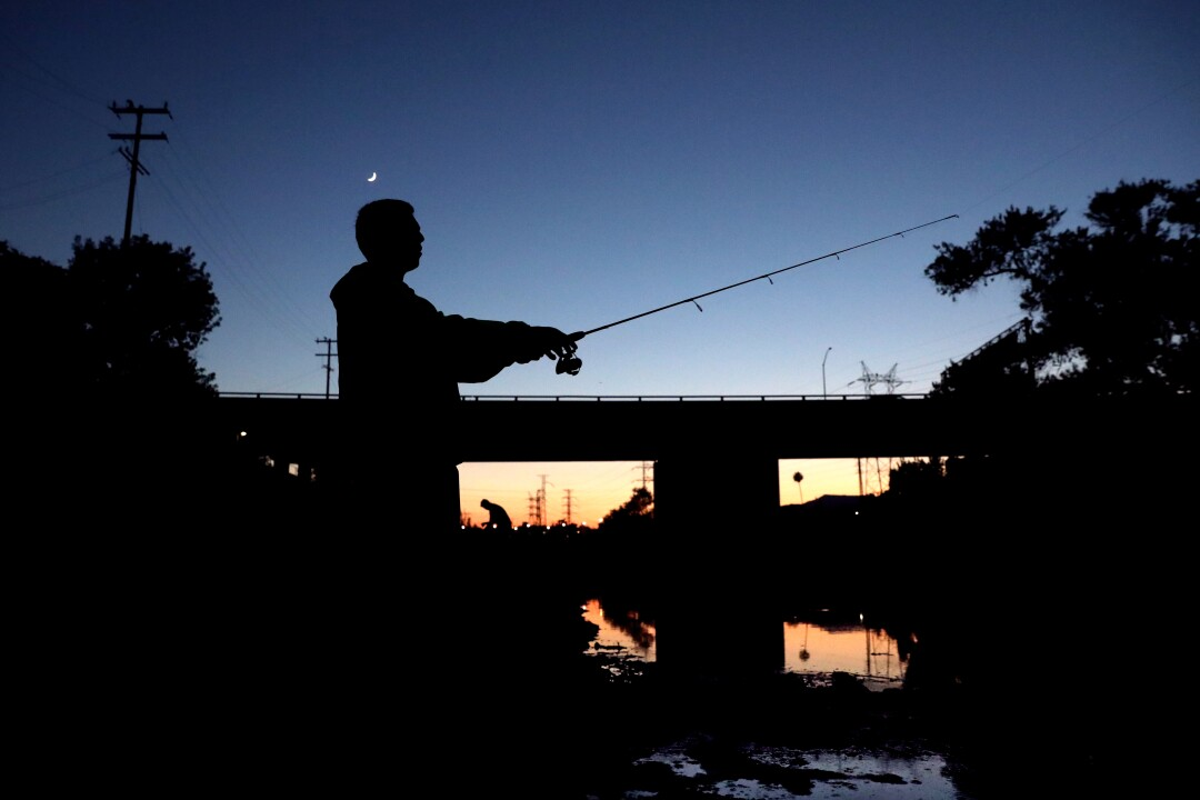 Alvarez, castging into the river, is silhouetted as the sun sets