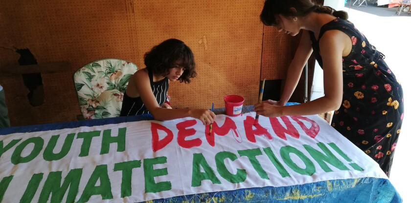 Ivonne Joy, a senior at High Tech High and Jess Weeden, a student at San Diego City College, painting a banner on Saturday, Sept. 7 for the international climate walkout on Friday, Sept. 20.