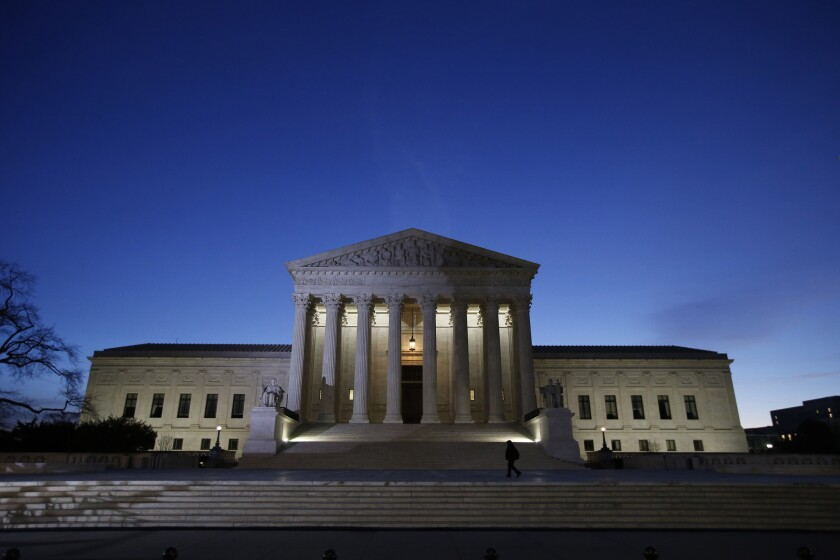 The U.S. Supreme Court building at night.