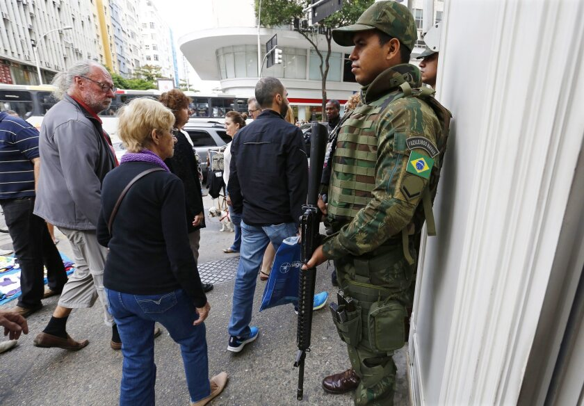 A Brazilian soldier stands guard on a corner in Copacabana.