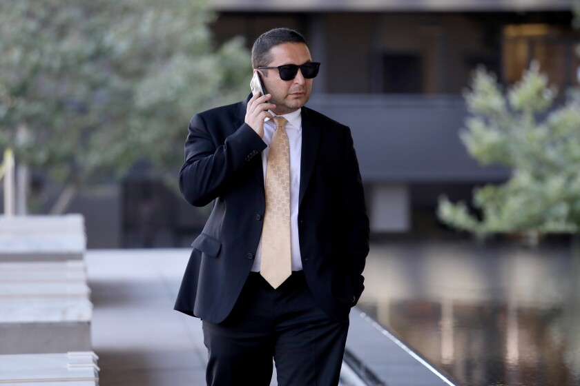 Artur Ayvazyan speaks on a cellphone outside a federal courthouse in downtown Los Angeles.