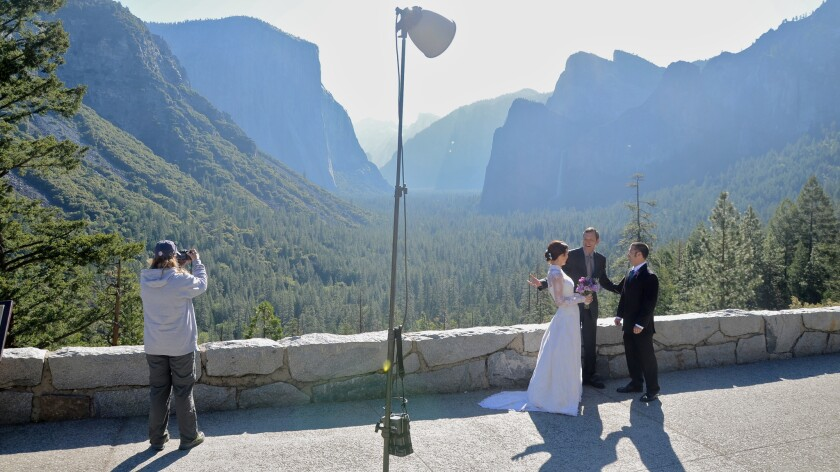 Early morning at Tunnel View at Yosemite National Park finds a happy couple busy tying the knot with the help of the park's leading wedding preacher, the Rev. Autrey Nasser.