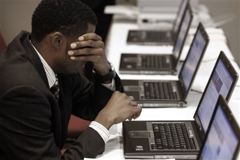 In this Nov. 4, 2009 photo,Terrell Collins, of Detroit, wipes his face while searching for employment on a laptop computer while attending a job fair in Livonia, Mich. The CEOs of America's largest companies said Tuesday, Dec. 8, 2009, that they do not expect employment to significantly improve in the next six months. (AP Photo/Paul Sancya)