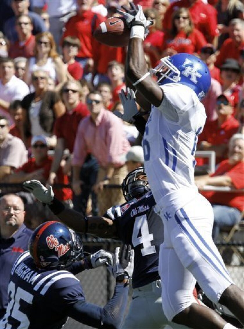 Kentucky wide receiver La'Rod King (16) leaps over Mississippi defenders Marcus Temple (4) and Fon Ingram (35) but still can't haul in a second quarter pass during an NCAA college football game in Oxford, Miss., Saturday, Oct. 2, 2010. (AP Photo/Rogelio V. Solis)