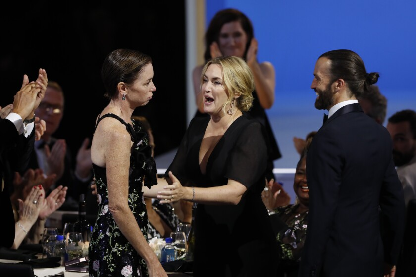 Julianne Nicholson, left, and Kate Winslet stand at a table at the Emmy Awards.