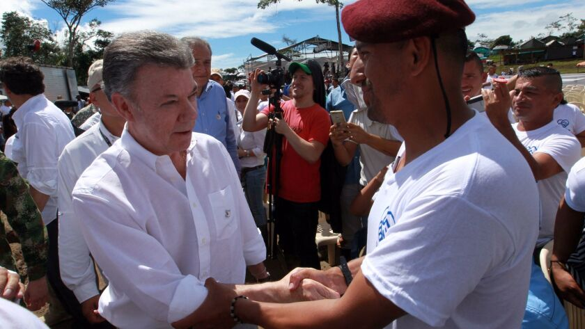 Colombian President Juan Manuel Santos, left, greets a FARC guerrilla during a disarmament ceremony in Mesetas, one of the rebel group's former strongholds, on June 27, 2017.