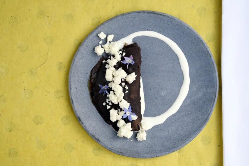 Taco Maria's enfrijolada: bean purée, lavender onions, queso fresco and garlic crema.