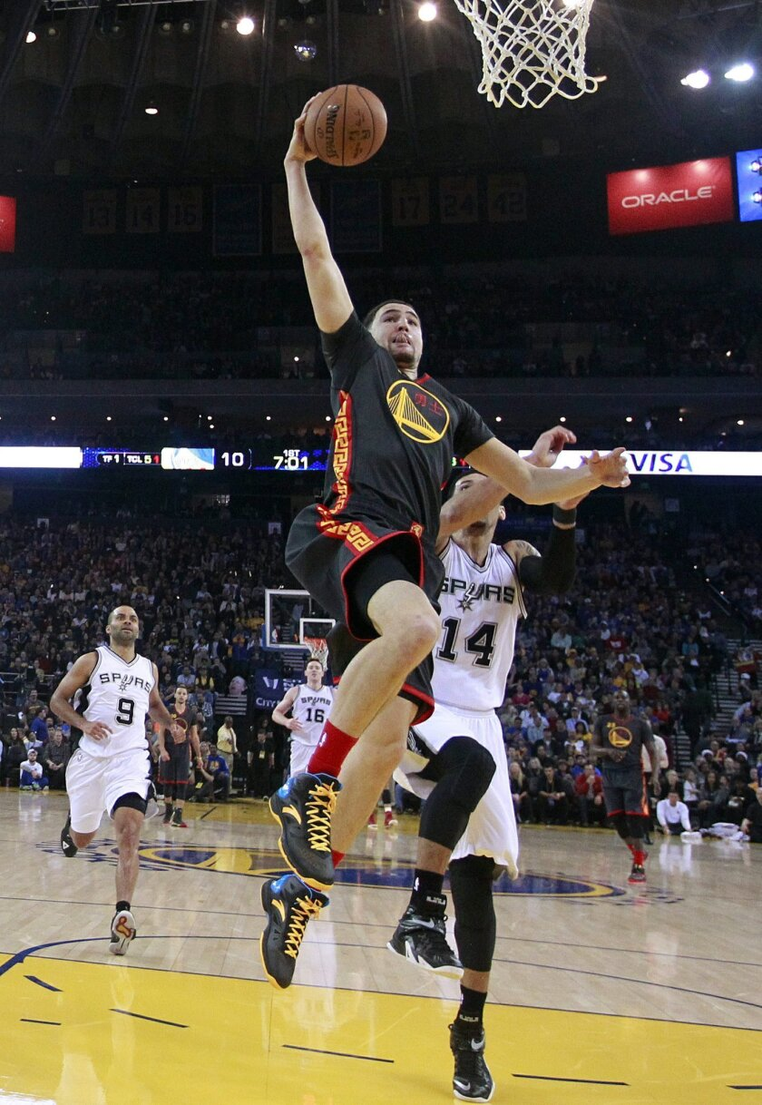 Golden State Warriors' Klay Thompson goes in for a dunk past San Antonio Spurs' Danny Green (14) during the first half of an NBA basketball game Friday, Feb. 20, 2015, in Oakland, Calif. (AP Photo/Marcio Jose Sanchez)