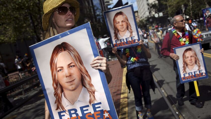 FILE PHOTO --  People hold signs calling for the release of imprisoned Wikileaks whistleblower Chelsea Manning while marching in a gay pride parade in San Francisco, California June 28, 2015.