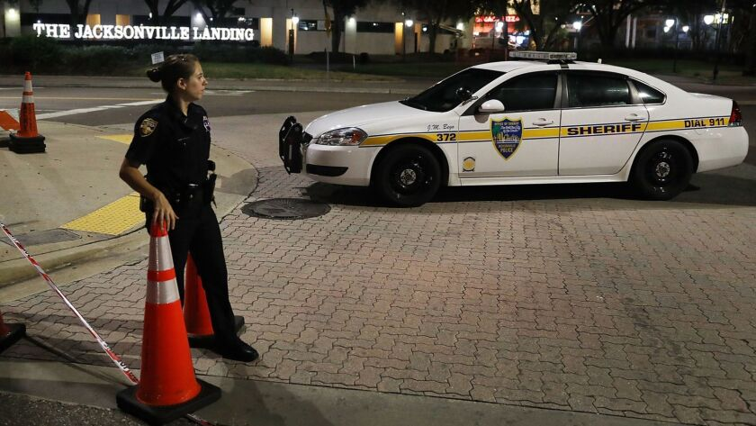 """A Jacksonville, Fla., sheriff's deputy guards the perimeter of the Jacksonville Landing complex on Monday after the mass shooting at a """"Madden NFL"""" tournament the day before."""