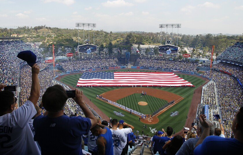 An American flag covers the field during the national anthem at Dodger Stadium on opening day 2016.