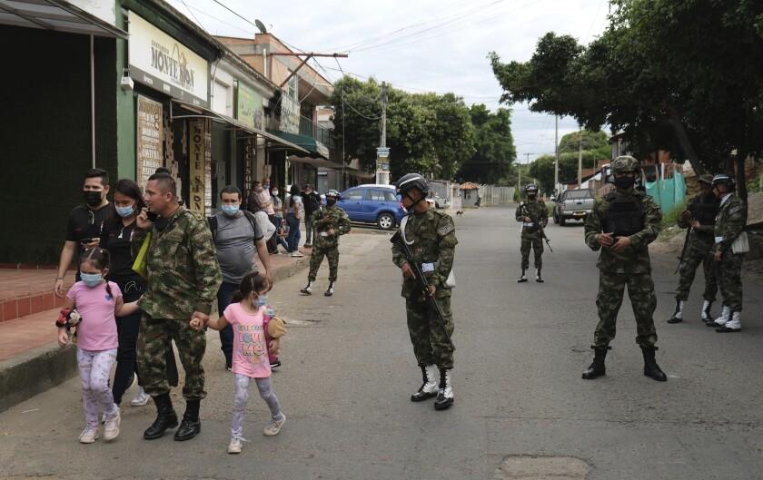 Un soldado camina con su familia cerca de la base militar donde explotó un coche bomba en Cúcuta, Colombia, el martes 15 de junio de 2021. (AP Foto/Ferley Ospina)