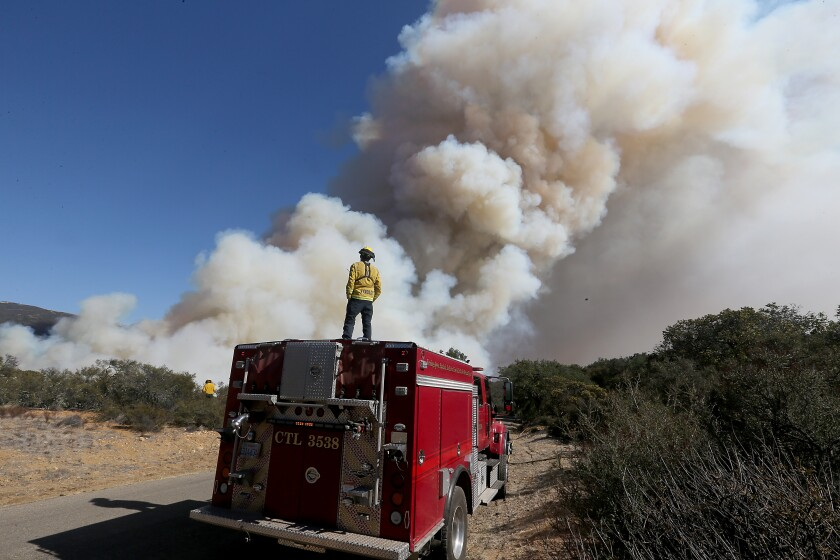 A firefighter is dwarfed by the plume of the Alisal fire near Goleta on Wednesday.