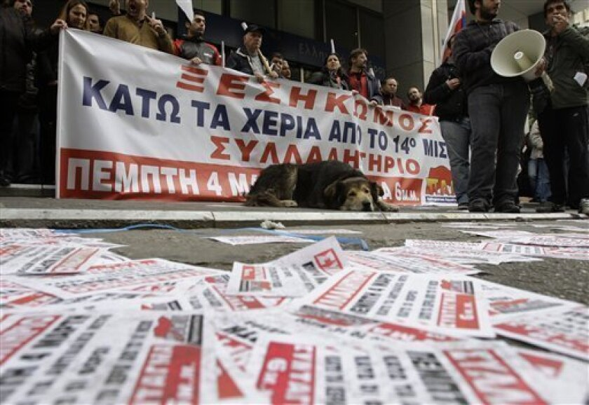 """Protesters hold a banner which read in Greek """"Revolt, Hands off the 14th Salary"""" outside the entrance of the Greek financial ministry in central Athens, Thursday, March 4, 2010. Dozens of Communist-affiliated unionists occupied the ministry building, preventing all employees from entering, to protest harsh austerity measures announced by the center-left government. Prime Minister George Papandreou has said he was forced to make deep spending cuts and tax hikes to save the debt-ridden country from bankruptcy. (AP Photo/Petros Giannakouris)"""