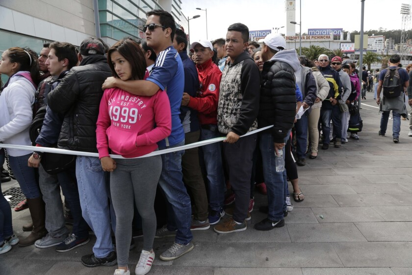 People line up to buy tickets to the first leg of the final Copa Libertadores matches between Ecuador's Independiente del Valle and Colombia's Atletico Nacional in Quito, Ecuador, Monday, July 18, 2016. The game is set for Wednesday. (AP Photo/Dolores Ochoa)