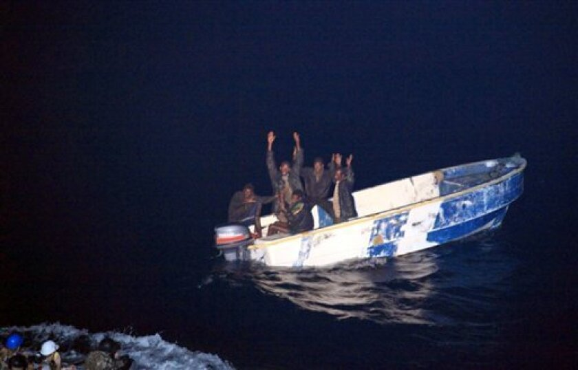 This photo released by the French Navy shows pirates holding their hands up to soldiers, left, of the French vessel La Somme, early Wednesday Oct.7, 2009 off the Somalia coast. Somali pirates in two skiffs fired on a French navy vessel early Wednesday after apparently mistaking it for a commercial boat, the French military said. The French ship gave chase and captured five suspected pirates.(AP Photo/Olivier Amalvict/ECPAD/French Navy) ** NO SALES