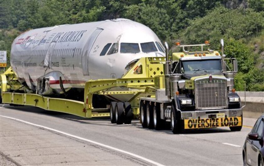 The fuselage of the US Airways plane that made a safe emergency landing in the Hudson River in 2009 is transported through Charleston, W.Va., on the way to a Charlotte N.C. museum Wednesday June 8, 2011. (AP Photo/The Daily Mail, Robert M. Wojcieszak)