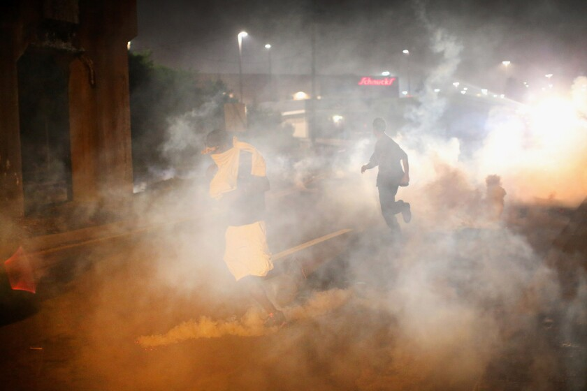 """Tear gas fills the street in Ferguson, Mo., on Sunday evening. Blacks and whites differ sharply over whether the police response has """"gone too far,"""" a new poll shows."""