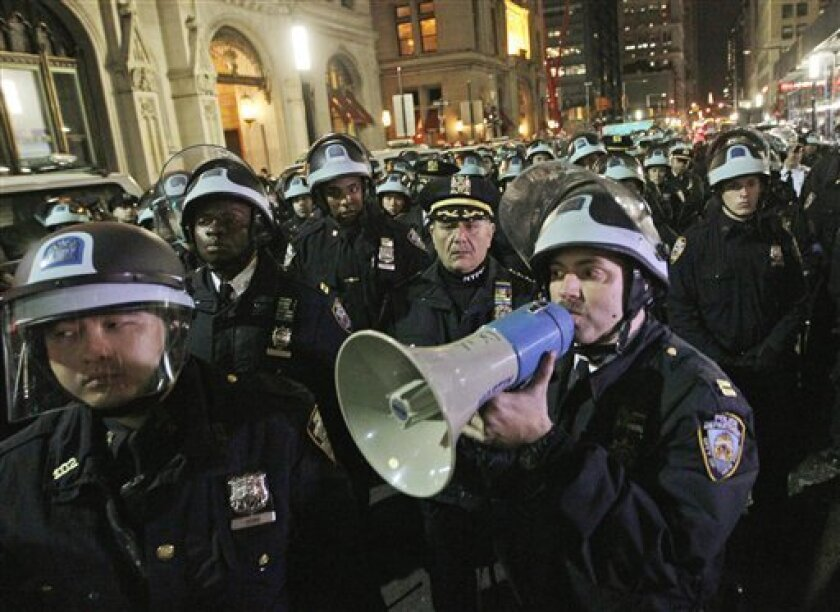 FILE- In this Nov. 15, 2011 file photo, police officers disperse Occupy Wall Street protesters near the encampment at Zuccotti Park in New York. A survey by the Associated Press shows that since the protests began, the Occupy Wall Street protests have cost local taxpayers at least $13 million in th