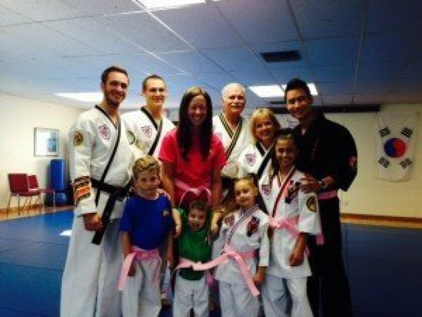 Del Mar Heights teacher Paige Rollins (center) with Sr. Master Wacholz's ATA Black Belt Academy staff, Xtreme Martial Arts founder Mike Chat, Paige Rollins' children Carter and Paxton (first and second from left), and Wish Warriors Channah Zeitung and Rayna Vallandingham (front row, right).