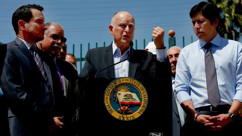 Gov. Jerry Brown stumps for the transportation bill in Riverside, flanked by Assembly Speaker Anthon