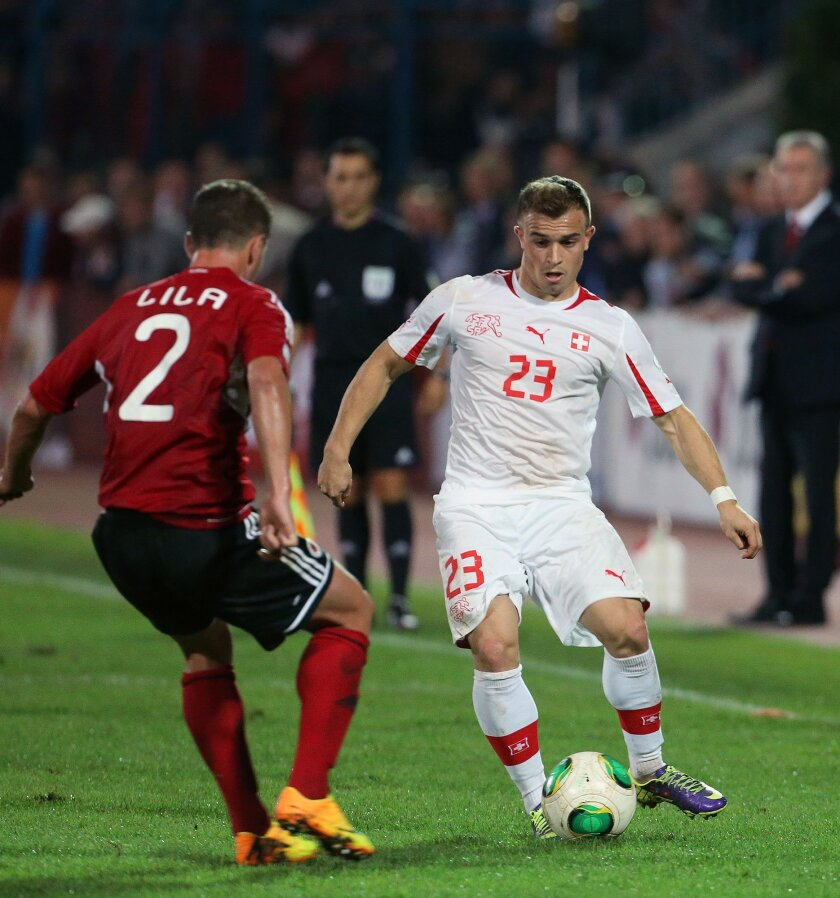 FILE - In this Friday, Oct. 11, 2013 file photo, Albania's Andi Lila, left, fights for the ball with Switzerland's Xherdan Shaqiri during their World Cup Group E qualifier soccer match in Tirana. The European Championship has a reputation for being the soccer fans' favorite tournament on the global