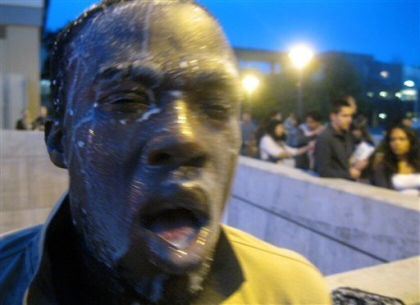 In this photo provided by David Steinman, Nnaemeka Alozie, campaign manager for Steinman, reacts with milk on his face after being sprayed with pepper spray during a protest on Tuesday, April 3, 2012, in Santa Monica, Calif. Campus police pepper-sprayed as many as 30 demonstrators after Santa Monica College students angry over a plan to offer high-priced courses tried to push their way into a trustees meeting Tuesday evening, authorities said. (AP Photo/Courtesy David Steinman)