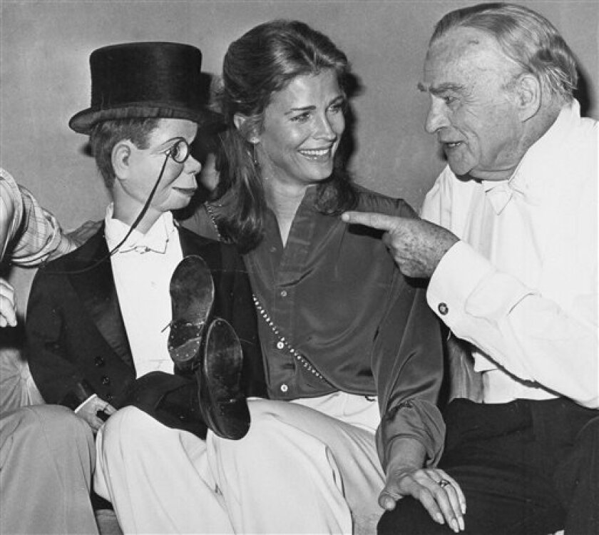 FILE - This Sept. 30, 1978 file photo shows dummy Charlie McCarthy crossing his legs on the lap of actress Candice Bergen as her father, ventriloquist Edgar Bergen, points at Caesar's Palace Hotel in Las Vegas at Edgar Bergen's farewell performance before his intended retirement.  He died in his sl