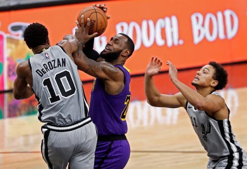 LeBron James (c), de Los Angeles Lakers disputa una bola contra DeMar DeRozan (i) y Bryn Forbes (d), de los San Antonio Spurs, el pasado 8 de diciembre. EFE/Archivo