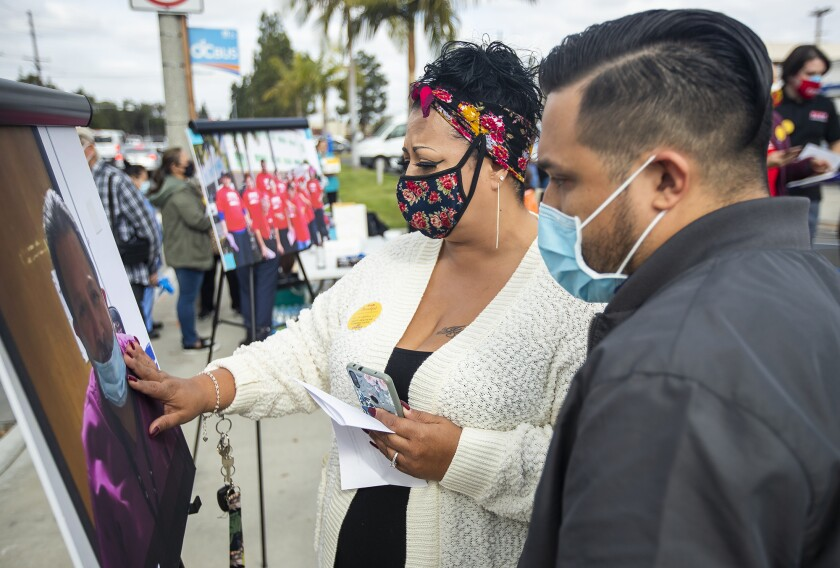 Irene Santos and Matthew Rodriguez look at a photograph of their father, Armando Rodriguez, who died of COVID-19.