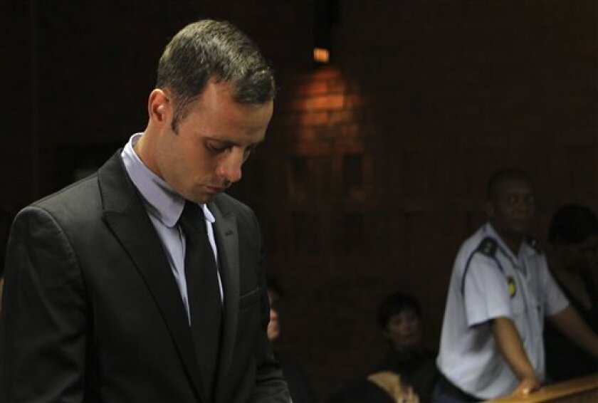 """Olympic athlete Oscar Pistorius stands inside the court as a police officer looks on during his bail hearing at the magistrate court in Pretoria, South Africa, Wednesday, Feb. 20, 2013. A South African judge says defense lawyers will need to offer """"exceptional"""" reasons to convince him to grant bail"""