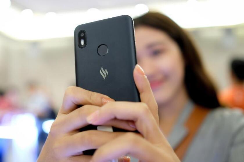 Una joven sostiene un teléfono móvil durante el lanzamiento de la primera marca de smartphones del conglomerado vietnamita Vingroup, diseñados y desarrollados por la firma española BQ, en Ho Chi Minh, Vietnam, hoy, 14 de diciembre de 2018. EFE