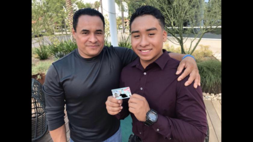 César Miguel Mejía Pérez junto a su padre Hector, muestra su tarjeta de residencia con orgullo.