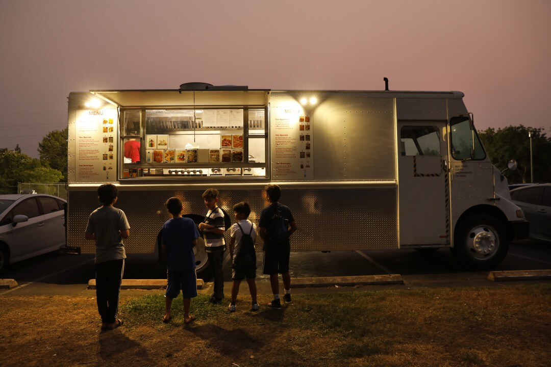 Children gathered at a food truck