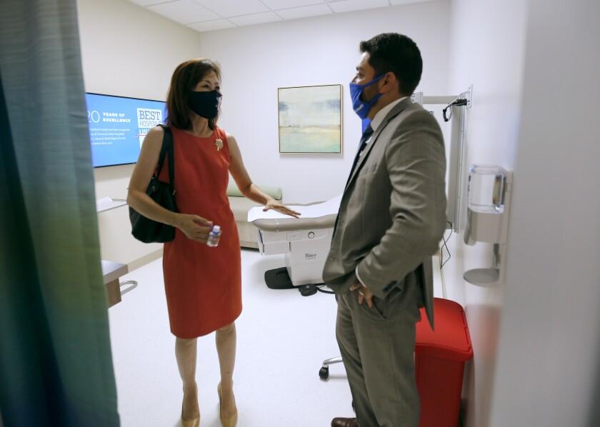 Michelle Steel, left, speaks with UCI Health Newport Beach practice manager Mark Gonzalez in August 2020.
