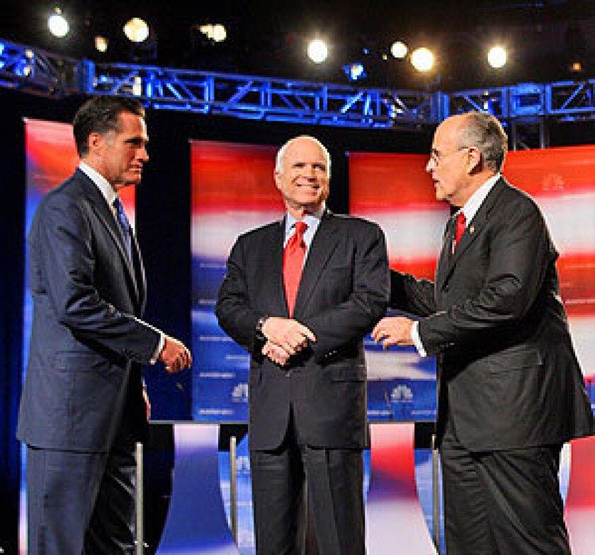 Republican presidential hopefuls Mitt Romney, John McCain and Rudy Giuliani greet each other at the start of the debate.