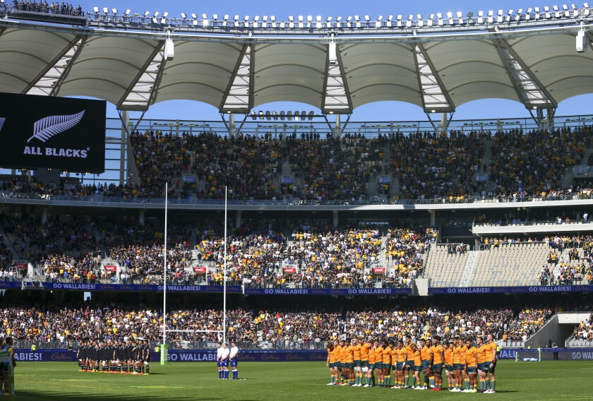 Teams lineup ahead of the Rugby Championship game between the All Blacks and the Wallabies in Perth, Australia, Sunday, Sept. 5, 2021. While the cities of Sydney and Melbourne in the east have been in strict lockdown, the Western Australia state capital Perth has largely remained open for business behind its closed border. Masks are rarely seen and bars and nightclubs are open. But states that remain virtually COVID-free, including Western Australia, are now under mounting pressure to share the nation's pandemic pain by opening their borders in the interests of opening the national economy. (AP Photo/Gary Day)
