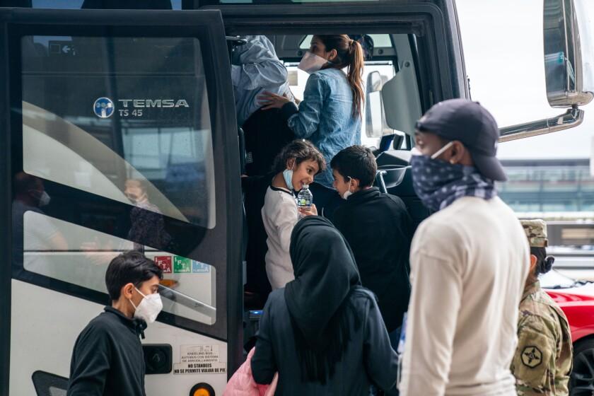 به نظر می رسد یک دختر و یک پسر در حال تماشای مسابقه تماشا هستند ، زیرا افراد نجات یافته سوار اتوبوس می شوند