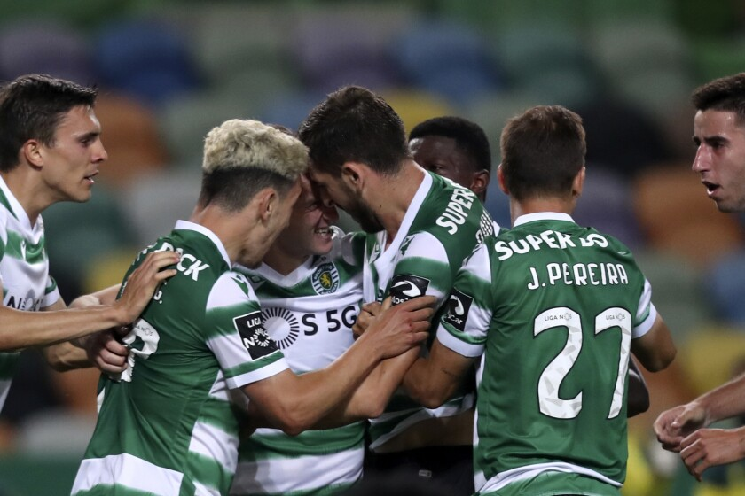 Sporting players celebrate after Paulinho, center right, scored the opening goal during the Portuguese League soccer match between Sporting CP and Boavista FC at the Alvalade stadium in Lisbon, Tuesday, May 11, 2021. (AP Photo/Pedro Rocha)