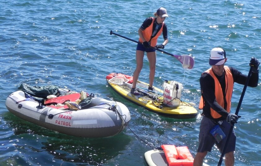 Couple Patti and Lorenzo Diaz employ their stand-up paddleboards to scoop up trash. They started H20 Trash Patrol, a nonprofit dedicated to protecting waterways.