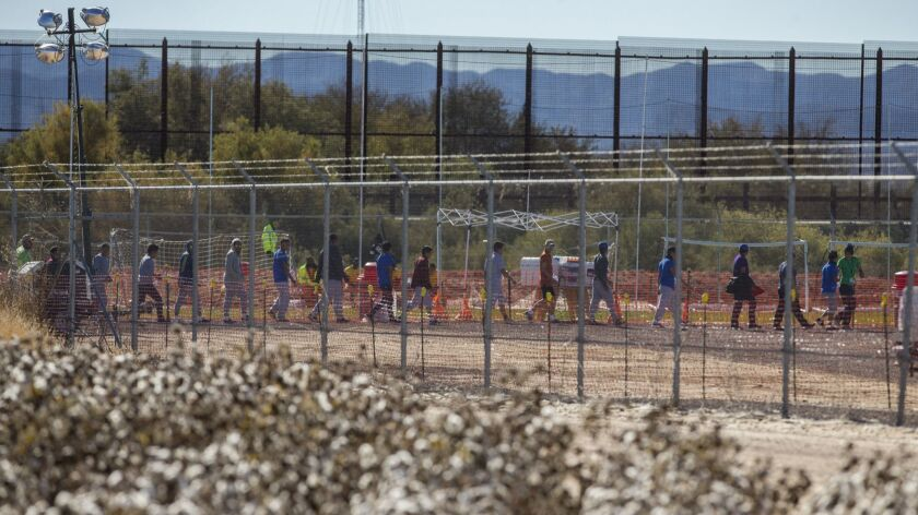In this Nov. 15, 2018 photo provided by Ivan Pierre Aguirre, migrant teens are led in a line inside