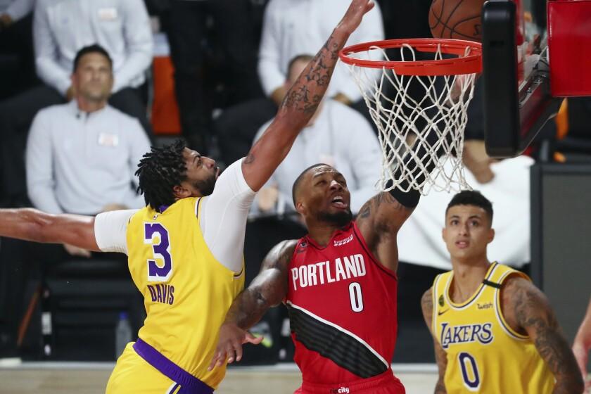 Lakers forward Anthony Davis blocks a shot by Trail Blazers guard Damian Lillard.