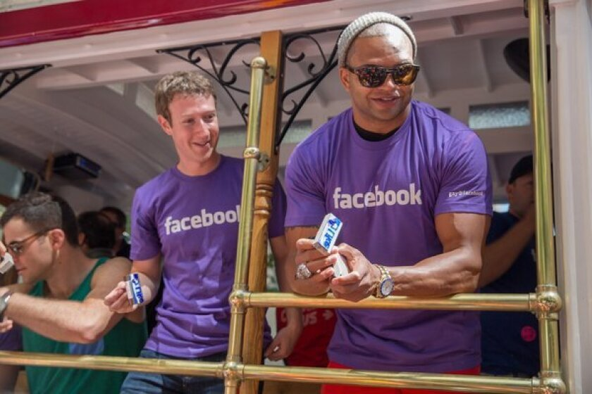 Mark Zuckerberg participates in San Francisco's gay pride parade Sunday along with NFL linebacker and same-sex marriage advocate Brendon Ayanbadejo, right.
