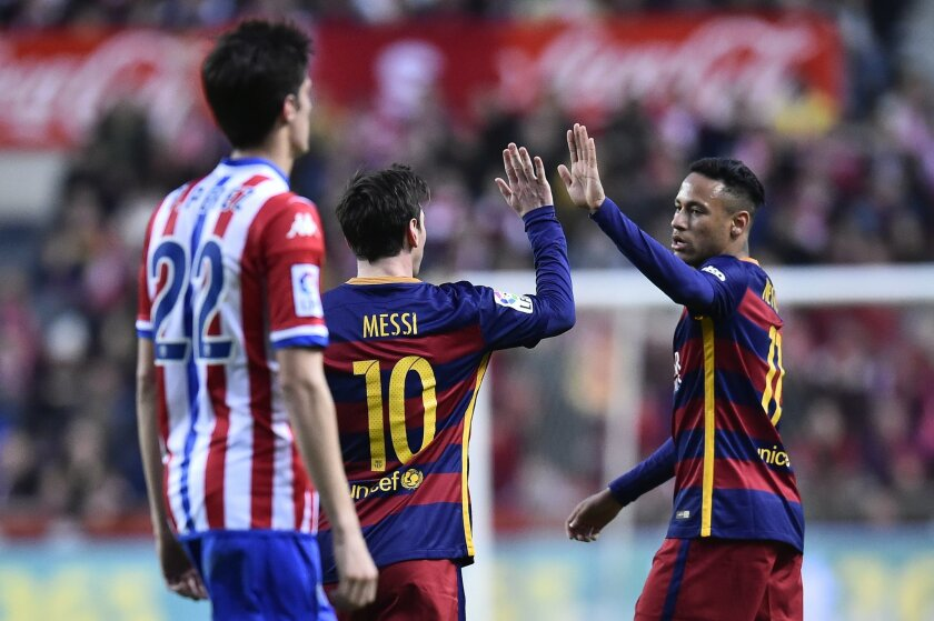 FC Barcelona's Lionel Messi, center, celebrates with Neymar after scoring a goal during their Spanish La Liga soccer match between Sporting de Gijon and FC Barcelona, at El Molinon stadium, in Gijon, northern Spain, Wednesday, Feb.17, 2016. (AP Photo/Alvaro Barrientos)