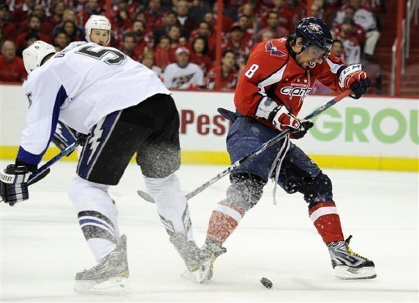 Washington Capitals left wing Alex Ovechkin (8), of Russia, battles for the puck against Tampa Bay Lightning defenseman Mattias Ohlund (5), of Sweden, during the first period in Game 1 of a semifinal NHL Stanley Cup hockey playoff series on Friday, April 29, 2011, in Washington. (AP Photo/Nick Wass)