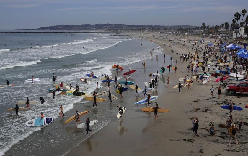 People walk into the water with surfboards and paddleboards