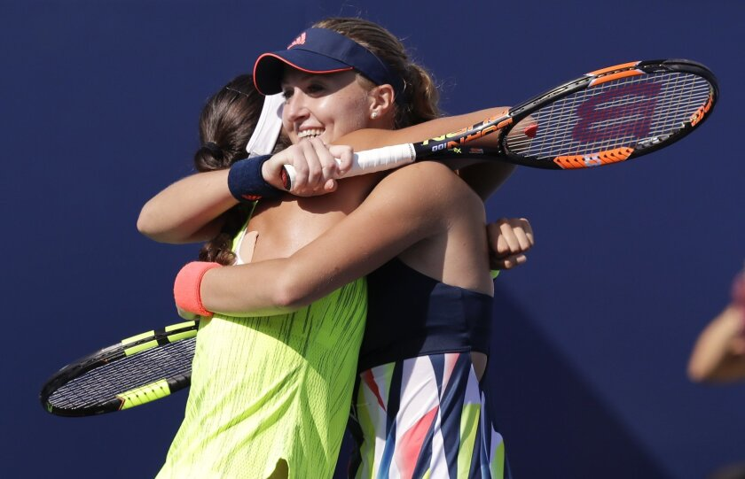 Kristina Mladenovic, of France, right, hugs doubles partner Caroline Garcia, of France, after winning their semifinal match against Martina Hingis, of Switzerland, and Coco Vandeweghe, of the United States, at the U.S. Open tennis tournament, Thursday, Sept. 8, 2016, in New York. (AP Photo/Charles