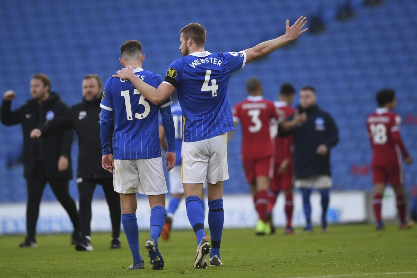 Brighton's Pascal Gross, left, and teammate Brighton's Adam Webster leave the pitch at the end of the English Premier League soccer match between Brighton and Hove Albion and Liverpool at the Amex stadium in Brighton, England, Saturday, Nov. 28, 2020. (Neil Hall/Pool Via AP)