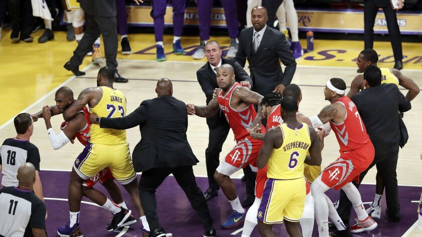 Houston's Chris Paul, far left, is held back by LeBron James after Paul fought with Rajon Rondo, far right, late in the Lakers' home opener.
