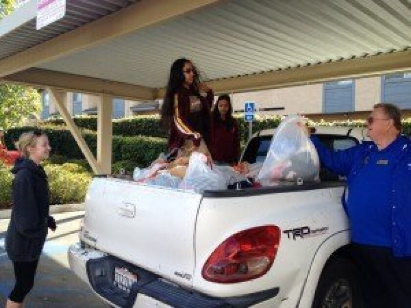 Club members packing a trunk with warm clothes for North County Solutions for Change. Courtesy photo